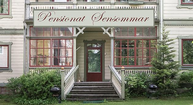 """Bild på ett hus med snickarglädje och skylten """"Pensionat Sensommar"""""""